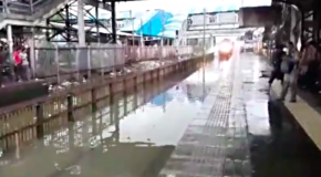 Train conductor speeds through flooded station and drenches commuters with dirty rainwater